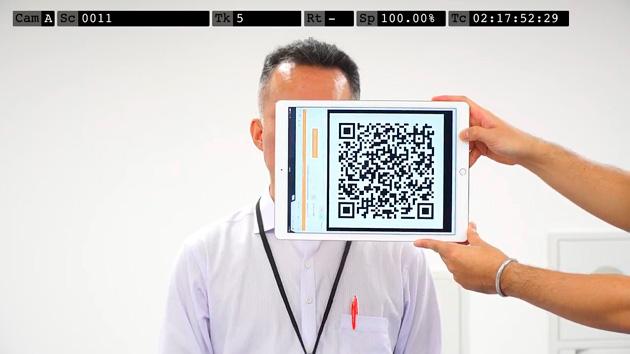 撮影開始の様子。「カチンコ」のようにQRコードを映す。 QRコードには、撮影シーンやカット番号などの情報が入っており、撮影動画をシステムにアップロードした際にQRコードが自動で識別され、仕分けがされる。